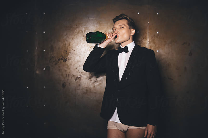 Men dressed in a suit and underpants drinking champagne by Andrey Pavlov for Stocksy United