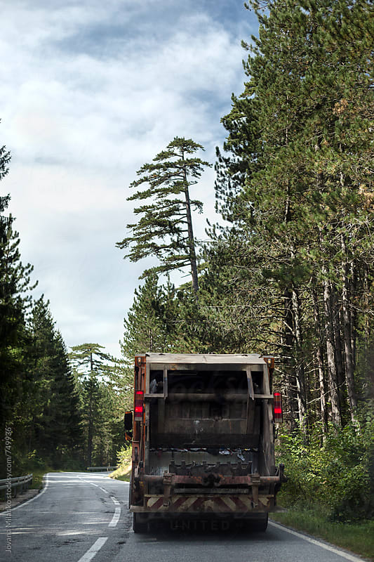 Garbage truck driving on a road trough the evergreen forest by Jovana Milanko for Stocksy United