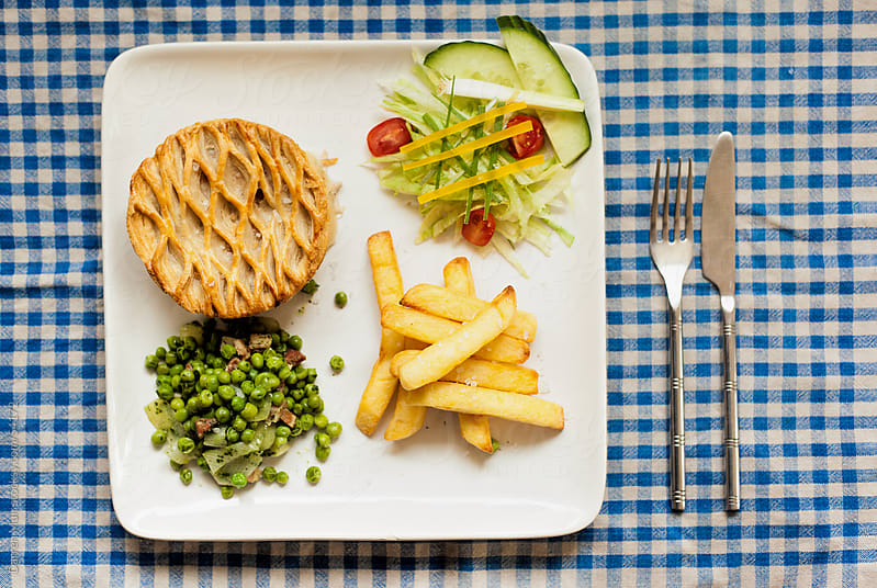 Chicken pie with chips and peas by Darren Muir for Stocksy United