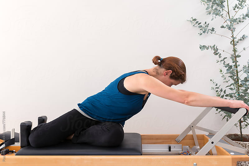 Pilates Reformer workout woman (30s) by Paul Phillips for Stocksy United