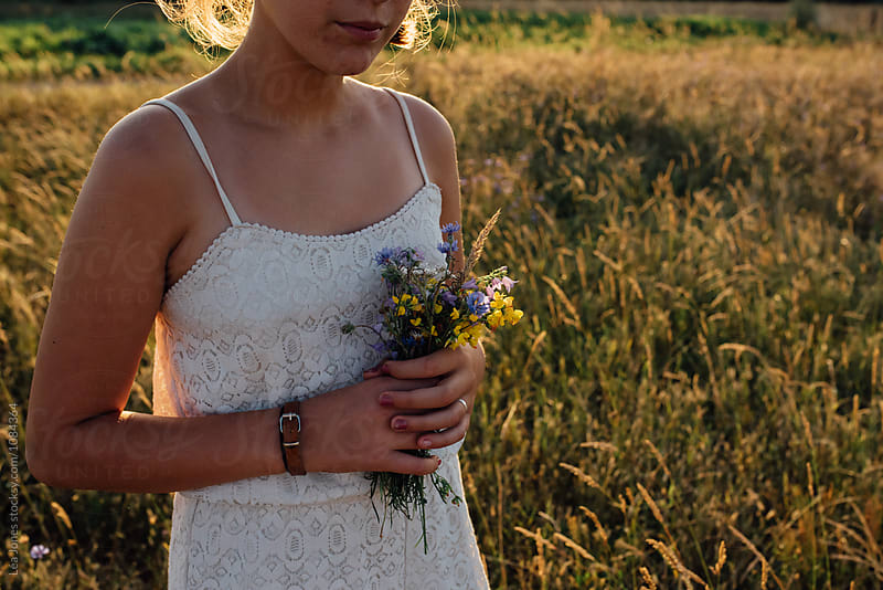 young woman picking flowers in the evening by Léa Jones for Stocksy United
