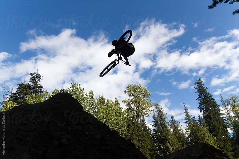 Bike jump silhouette. Tailwhip on dirt jumps by Alejandro Moreno de Carlos for Stocksy United
