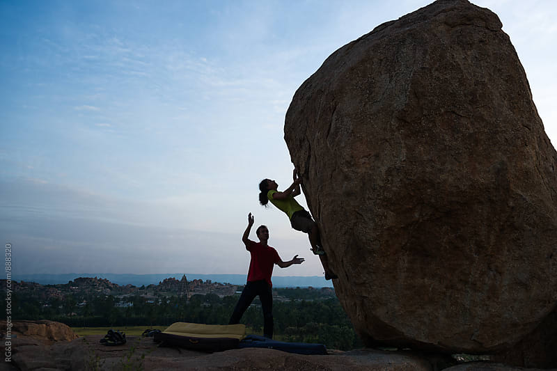 Couple rock climbing a boulder by RG&B Images for Stocksy United