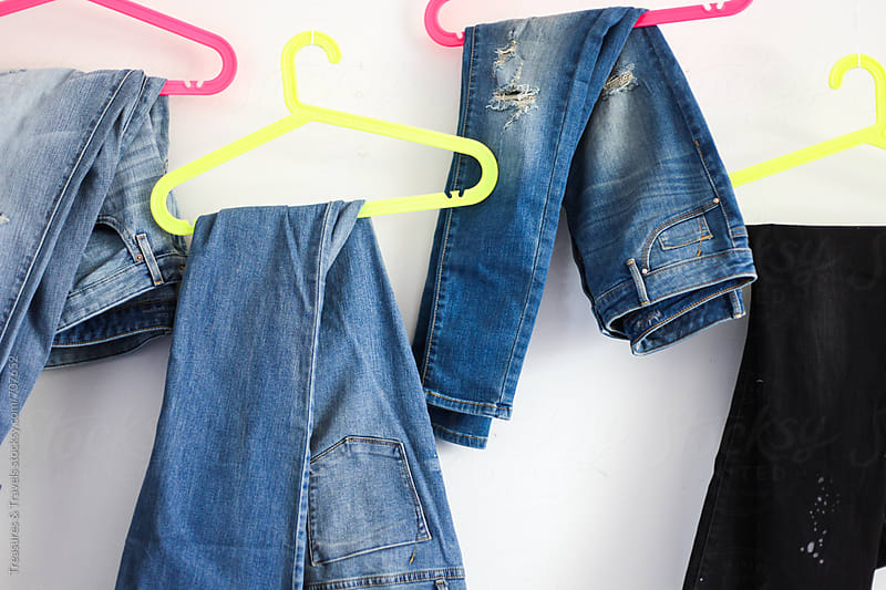 denim hanging on neon hangers by Treasures & Travels for Stocksy United