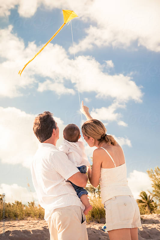 Happy Young Family of Three Flying a Kite at the Beach by Shelly Perry for Stocksy United