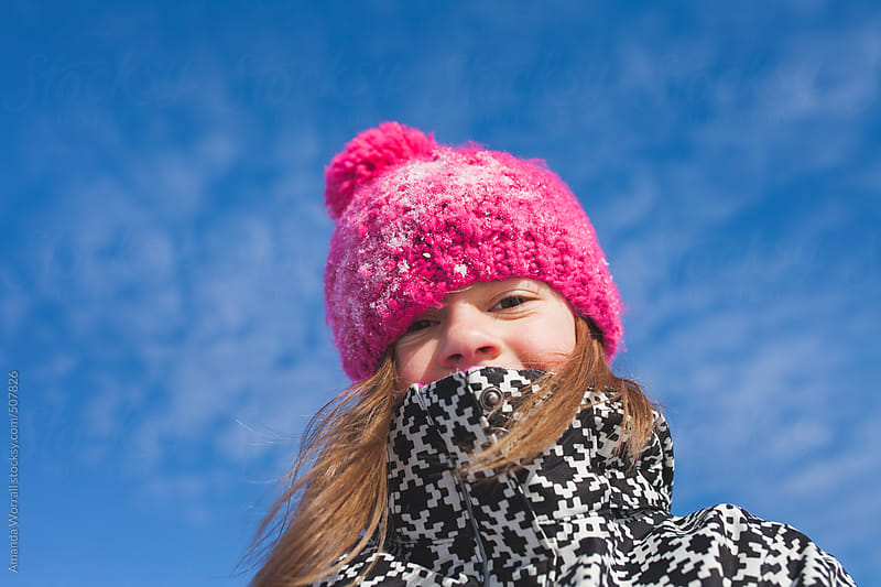 Young girl playing outside on sunny winter day by Amanda Worrall for Stocksy United