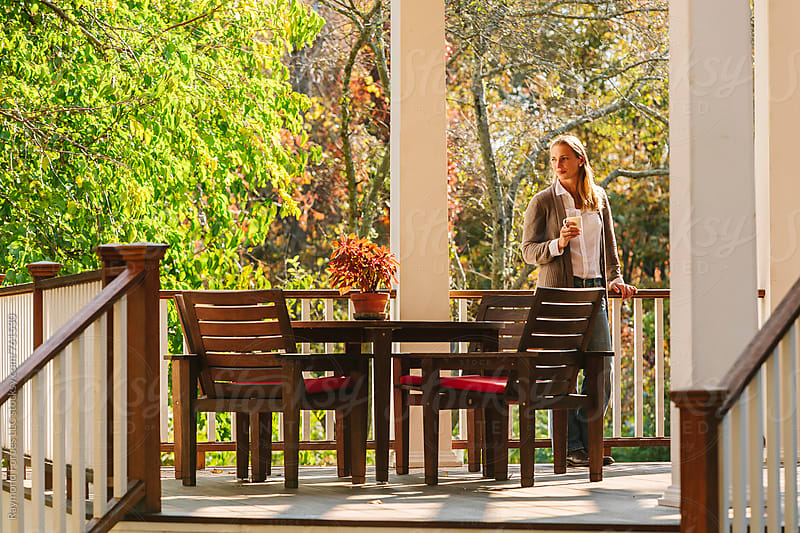 Woman on Porch Enjoying Autumn Day by Raymond Forbes LLC for Stocksy United