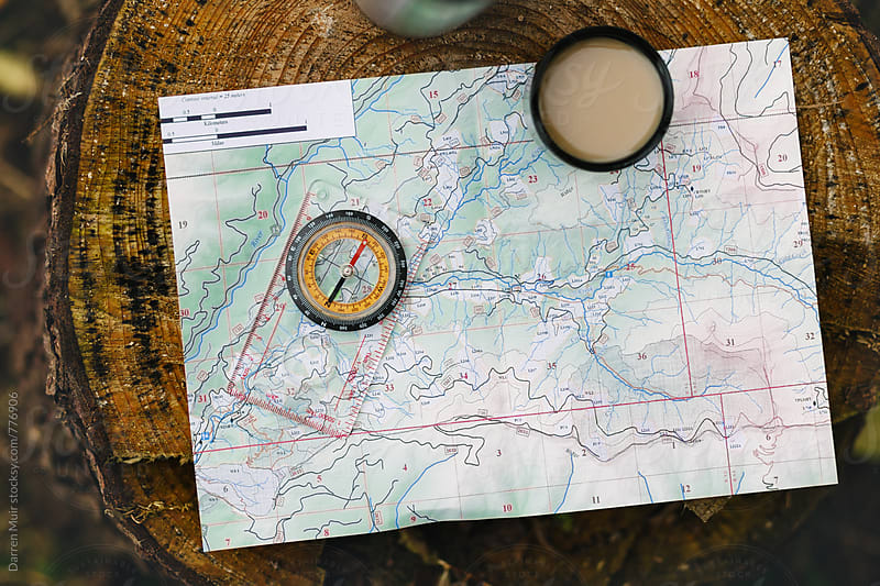 Map a compass and a coffee. by Darren Muir for Stocksy United