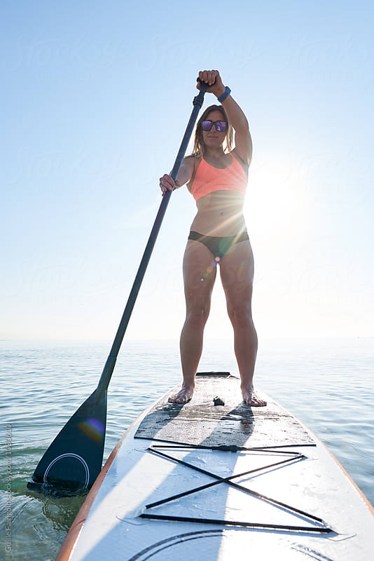 Portrait of surfer with paddle on board in sunlight by Guille Faingold for Stocksy United