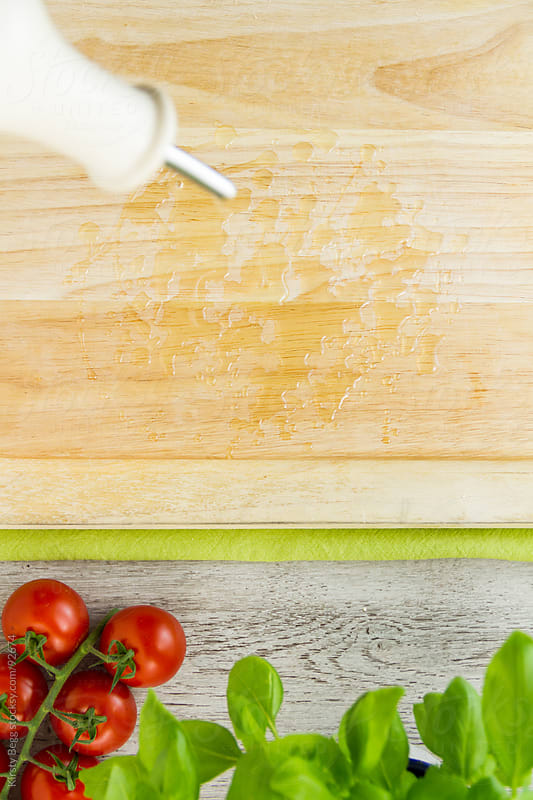 Oiling the chopping board with Italian ingredients by Kirsty Begg for Stocksy United