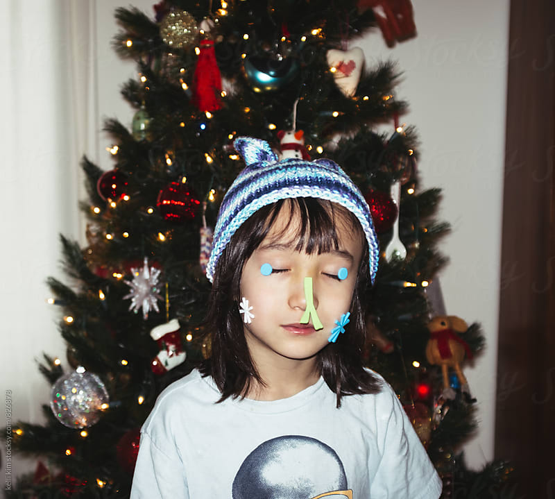 Young boy being silly with holiday stickers by kelli kim for Stocksy United