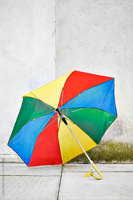 An open multi couloured umbrella left by a wall by James Ross for Stocksy United