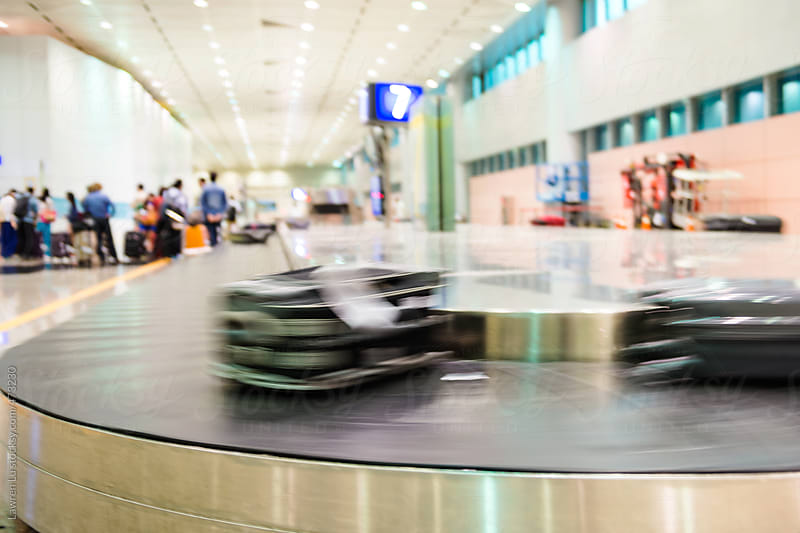 Luggage on airport carousel with bags round on conveyor until claimed, passengers visible in background by Lawren Lu for Stocksy United