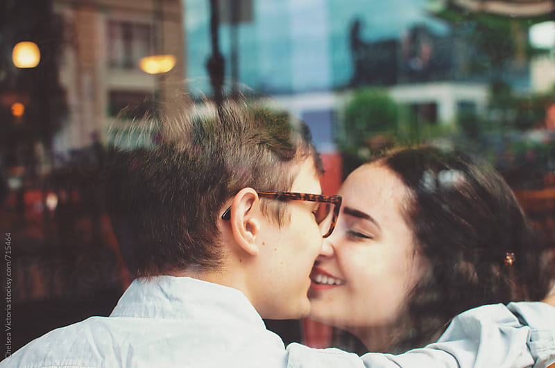 A young couple in the city through a cafe window by Chelsea Victoria for Stocksy United
