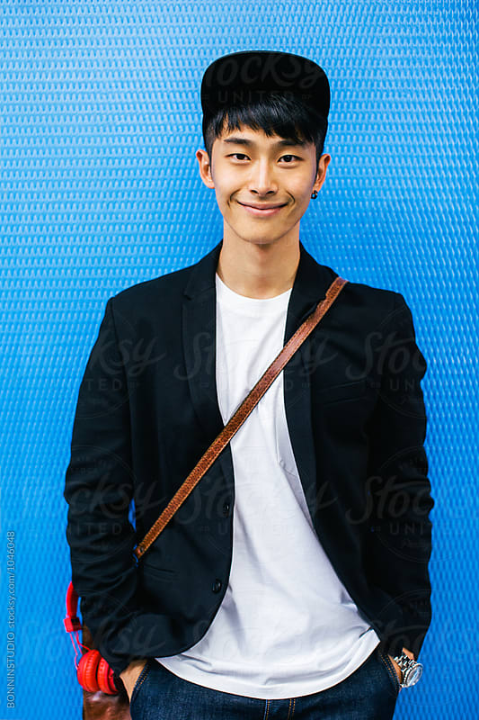 Portrait of a young asian businessman smiling looking at camera in front of a blue wall.  by BONNINSTUDIO for Stocksy United