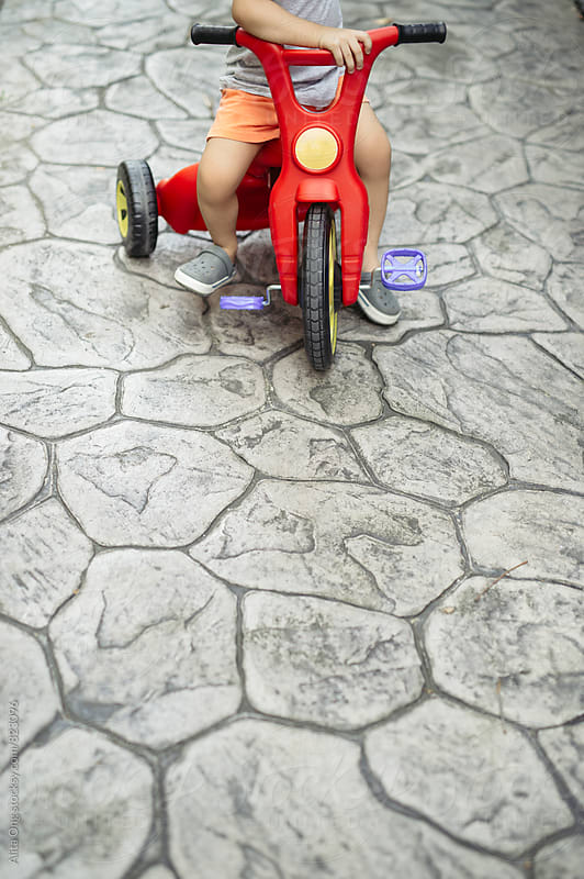 Little boy on his red bike by Alita Ong for Stocksy United
