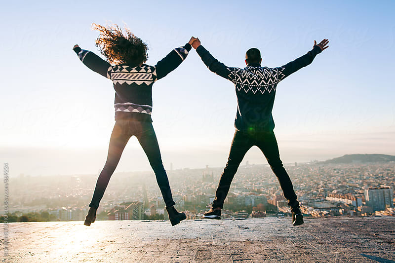 Back view of young couple jumping above Barcelona. by BONNINSTUDIO for Stocksy United