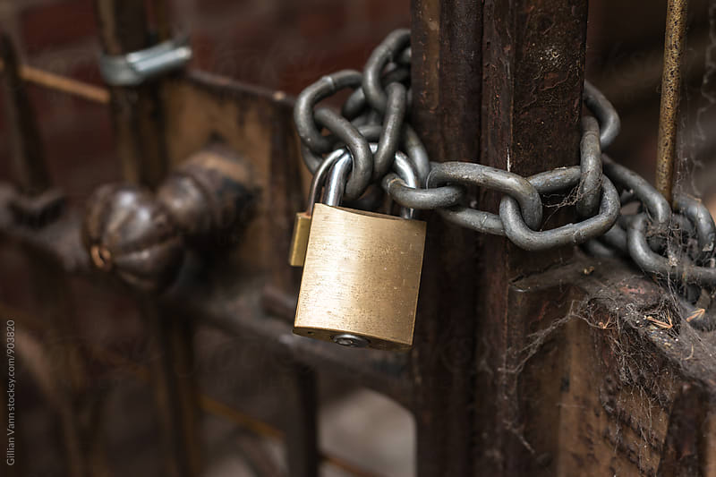 padlock with chain on a gate by Gillian Vann for Stocksy United