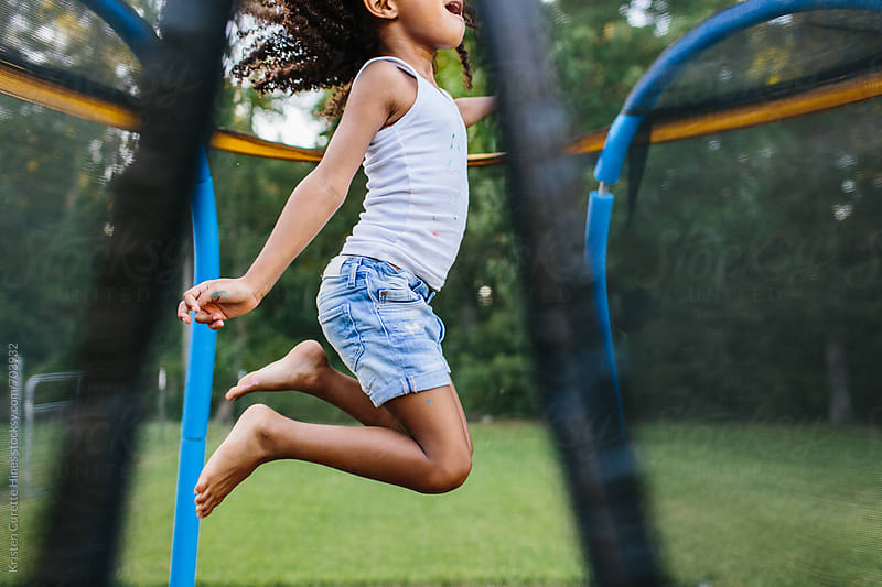 A young toddler having fun on a trampoline during the summer by Kristen Curette Hines for Stocksy United