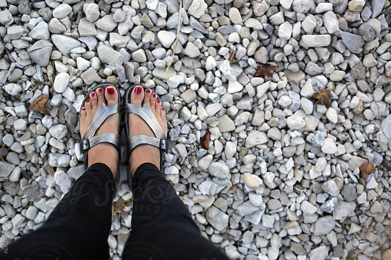 A Woman's Feet In Sandals. Standing On A Rocky Beach. by ALICIA BOCK for Stocksy United