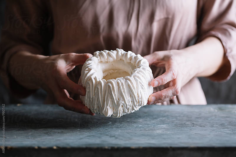 Close-up of woman holding pavlova cake with two hands by Alberto Bogo for Stocksy United