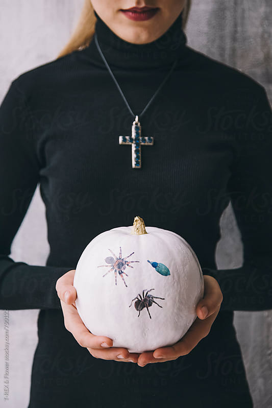 Woman holding white pumpkin with spiders by Danil Nevsky for Stocksy United
