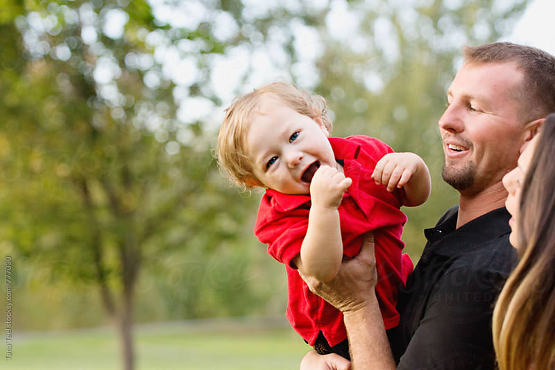father holds laughing child by Tana Teel for Stocksy United