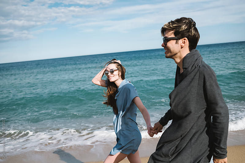 Young couple having fun at the beach by Simone Becchetti for Stocksy United
