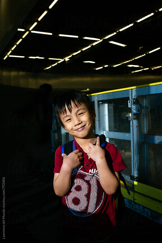 Young kid carryng a backpack while playfully smiling at the camera by Lawrence del Mundo for Stocksy United