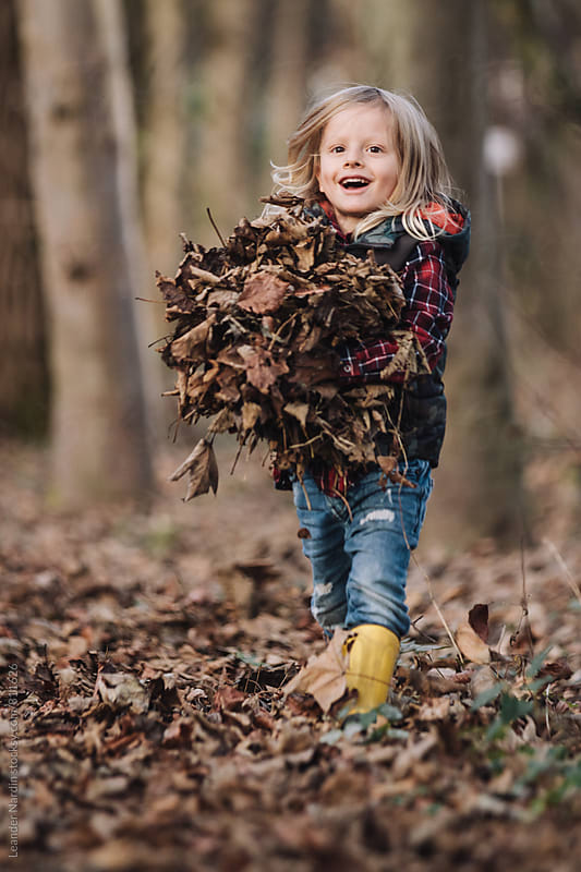 cute smiling little boy with yellow gumboots carrying hands full of leaves ready for a foliage battle by Leander Nardin for Stocksy United