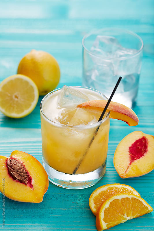Cocktail made with fresh peach, lemon, orange, and brandy by Trinette Reed for Stocksy United