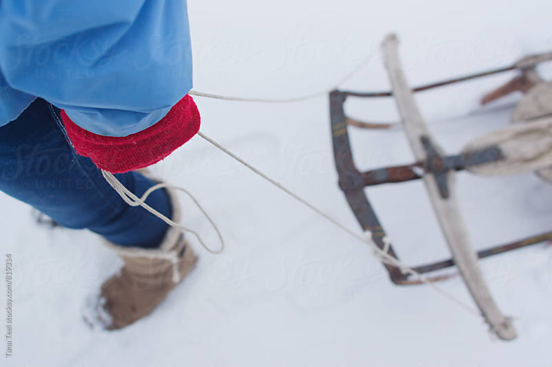 Downward view of gloved hand pulling old wooden sled through snow by Tana Teel for Stocksy United