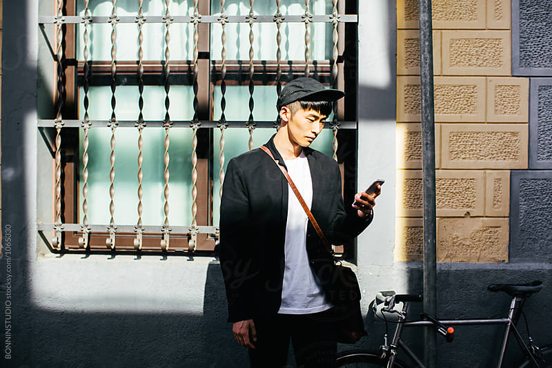 Businessman  using his phone standing with bicycle on the street.  by BONNINSTUDIO for Stocksy United