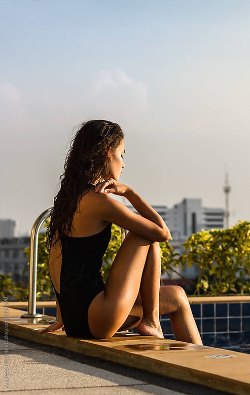 Beautiful young woman in swimsuit sitting by the pool on sunny day with city in background. by Audrey Shtecinjo for Stocksy United