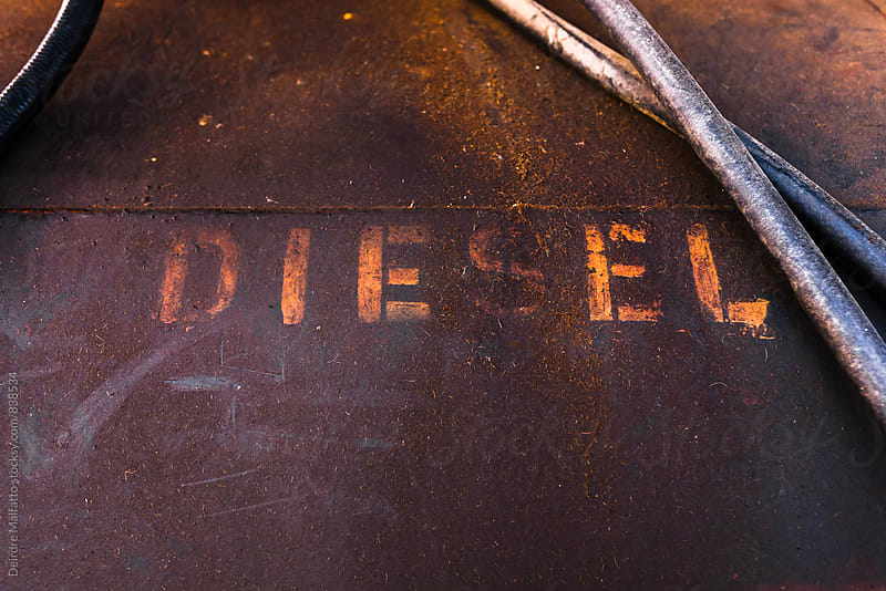 the word diesel stenciled on an old tank by Deirdre Malfatto for Stocksy United