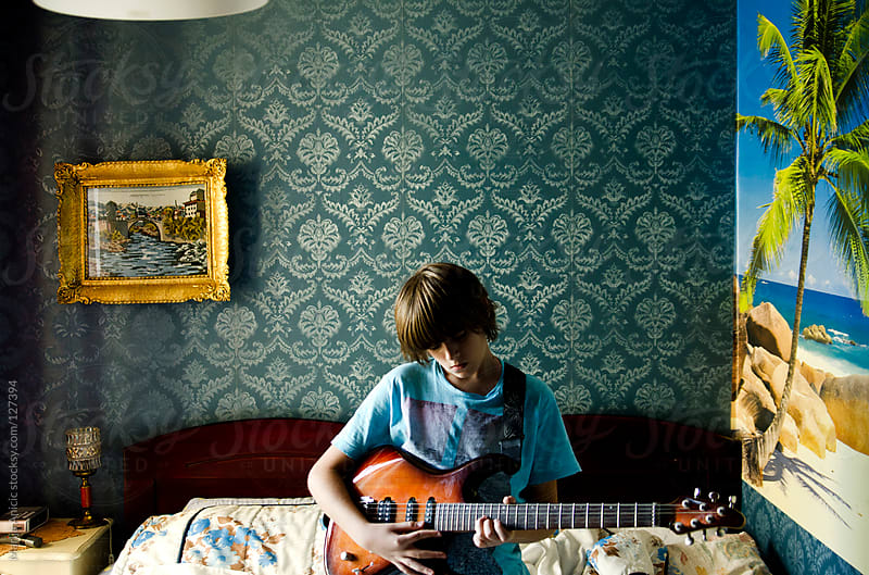 Boy is playing electric guitar in retro room  by Marija Anicic for Stocksy United
