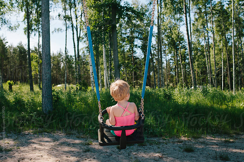 Little girl in swimsuit in a swing seen from behind. by Julia Forsman for Stocksy United