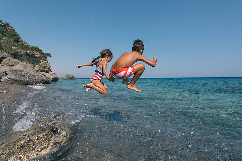 Children jumping in the sea by Dejan Ristovski for Stocksy United