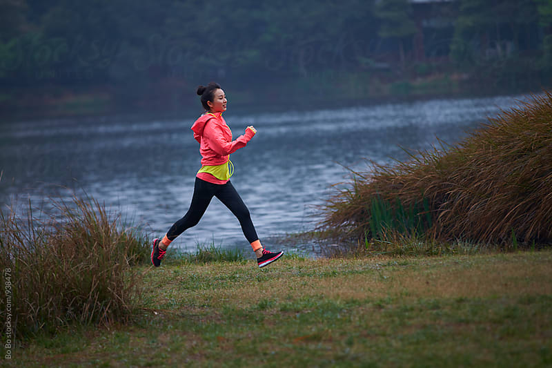 young woman running by the lake by Bo Bo for Stocksy United