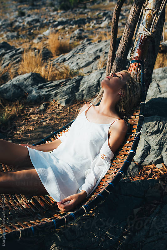 Young woman in white dress relaxing in hammock by Marija Savic for Stocksy United