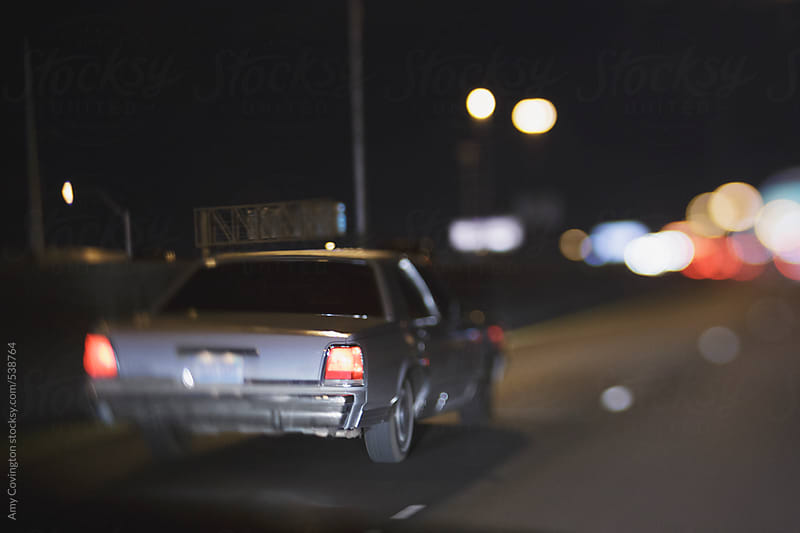 Older car on the highway at night by Amy Covington for Stocksy United