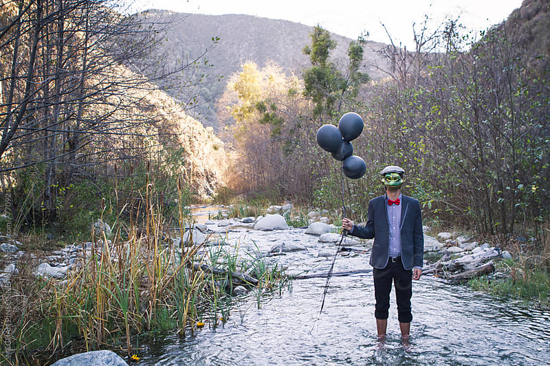 Man with Frog Mask and Balloons, Dreamy and Surreal by MEGHAN PINSONNEAULT for Stocksy United