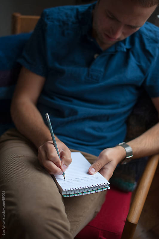 seated man writing in a notepad by Lee Avison for Stocksy United
