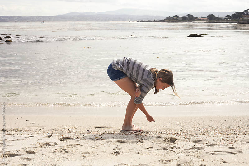 Young girl exploring on the beach in Monterey Bay by Carolyn Lagattuta for Stocksy United