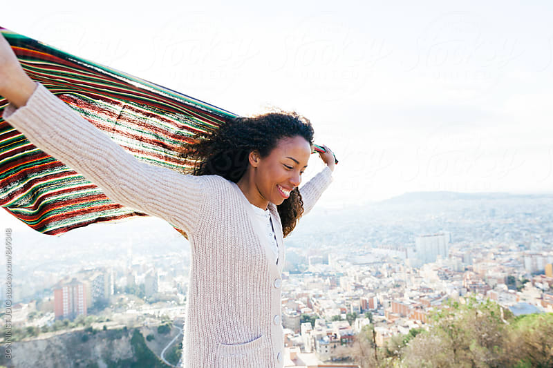 African american woman holding a blanket on a windy day above city. by BONNINSTUDIO for Stocksy United