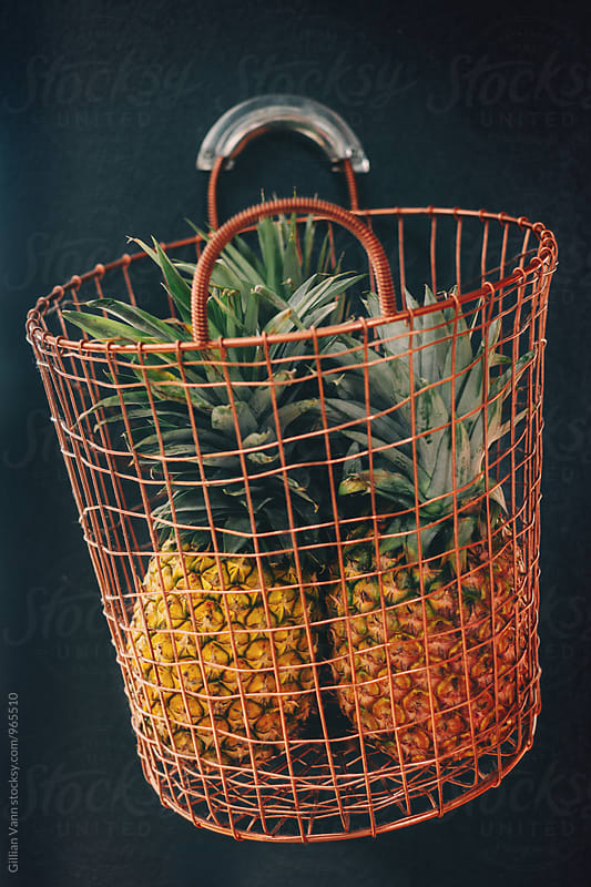 pineapples in a copper wire basket by Gillian Vann for Stocksy United
