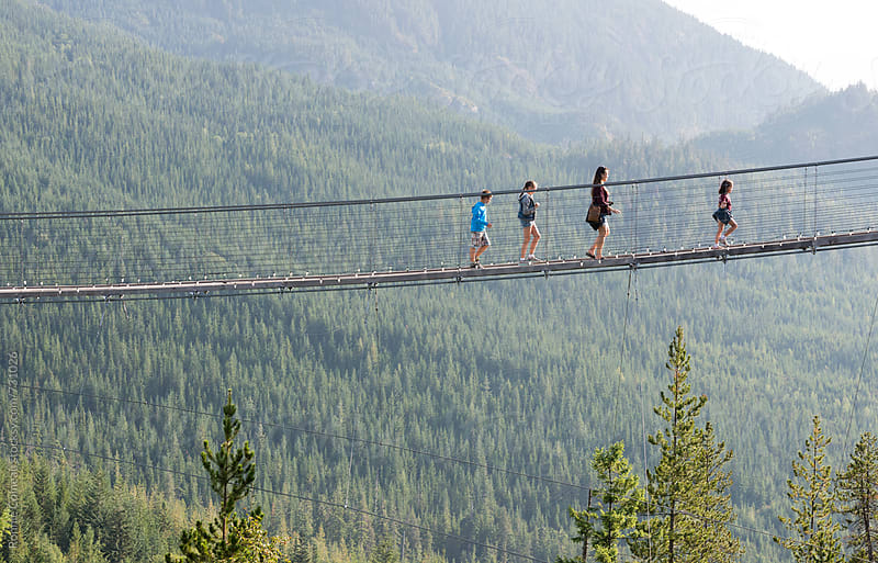 Family Crossing Suspension Bridge by Ronnie Comeau for Stocksy United
