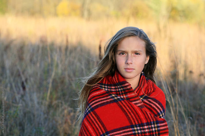 A Pretty Girl Standing In An Autumn Field Wrapped In A Warm Plaid Blanket by ALICIA BOCK for Stocksy United