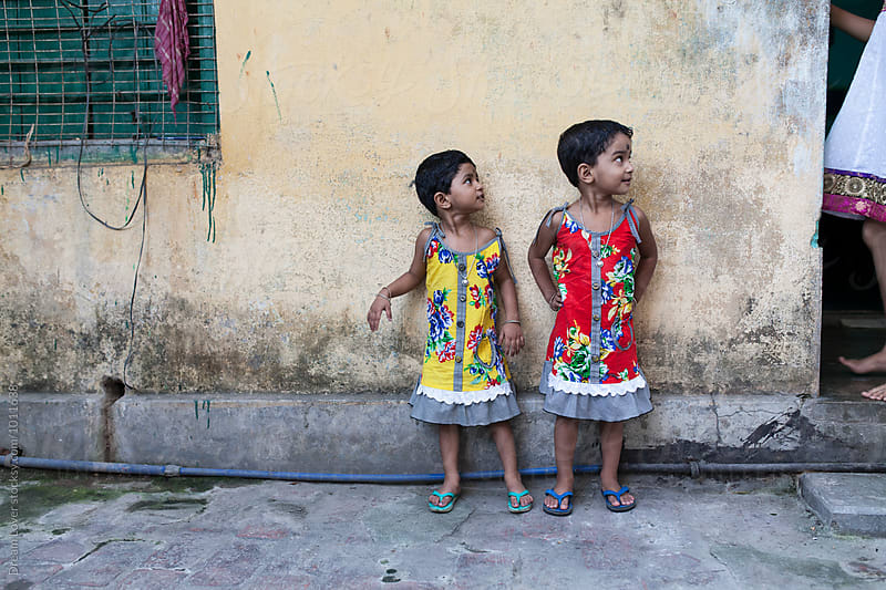 Twin girls looking sidewise by PARTHA PAL for Stocksy United