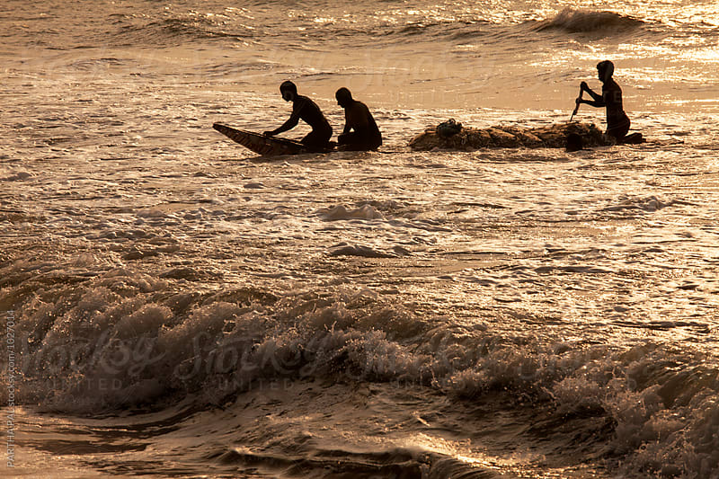 Silhouette of fishermen struggling with small boat to come near sea shore  by PARTHA PAL for Stocksy United